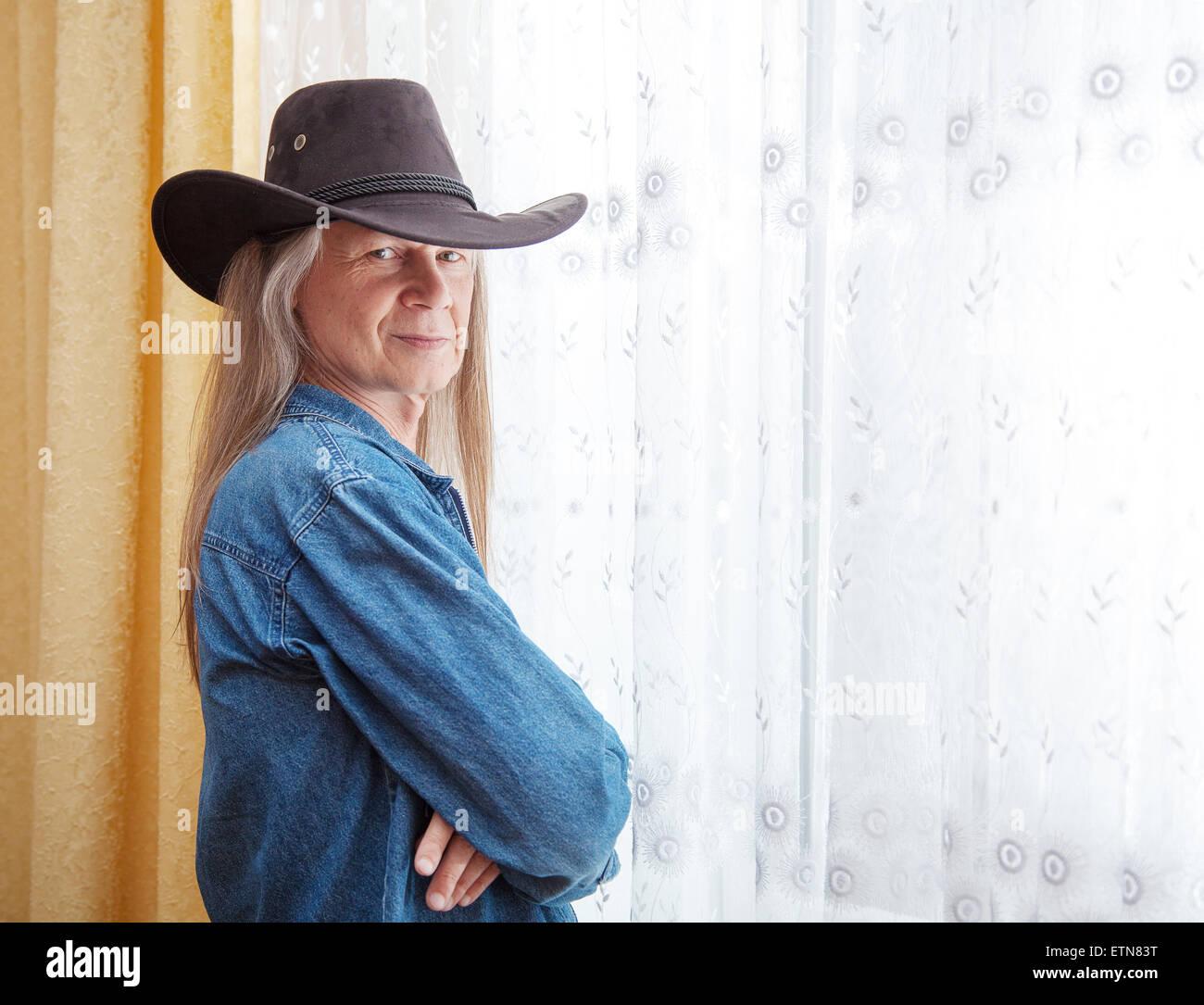 Ritratto di un uomo maturo con i capelli lunghi e un cappello da cowboy Immagini Stock