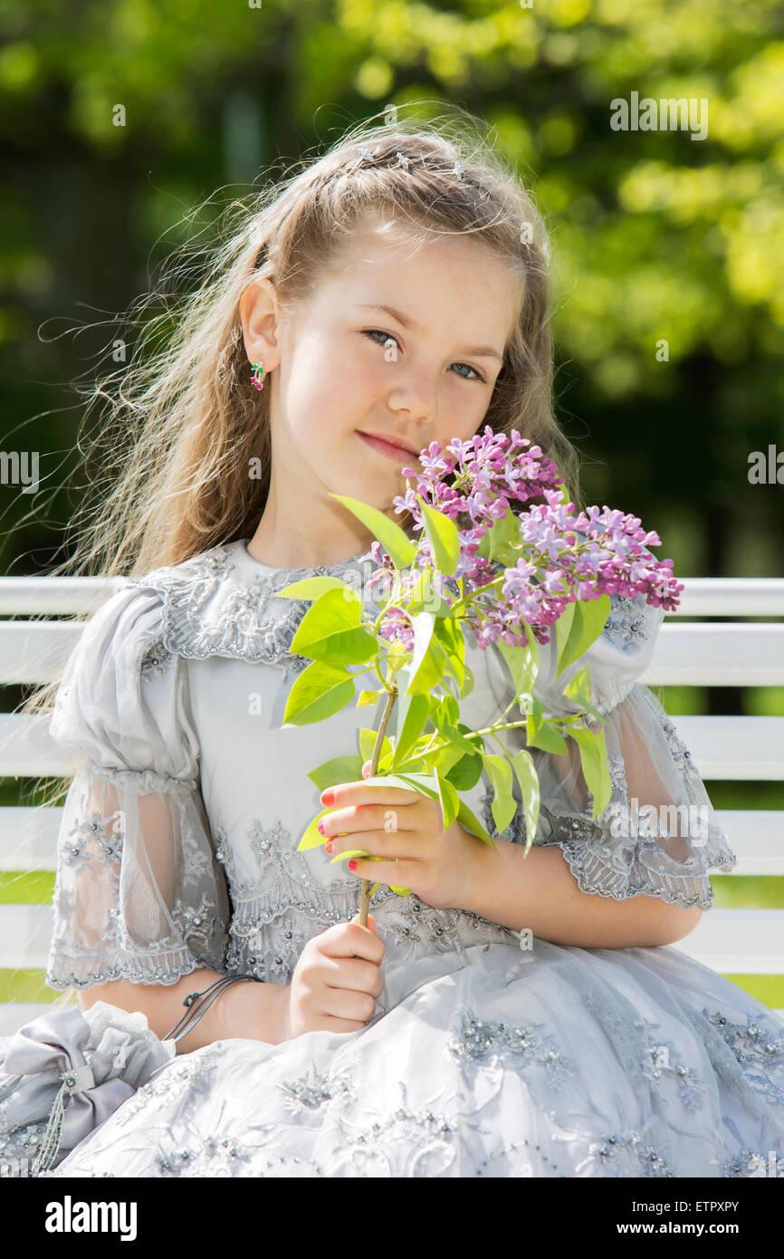 Ritratto di ragazza tenendo fiori vicino il suo volto Immagini Stock