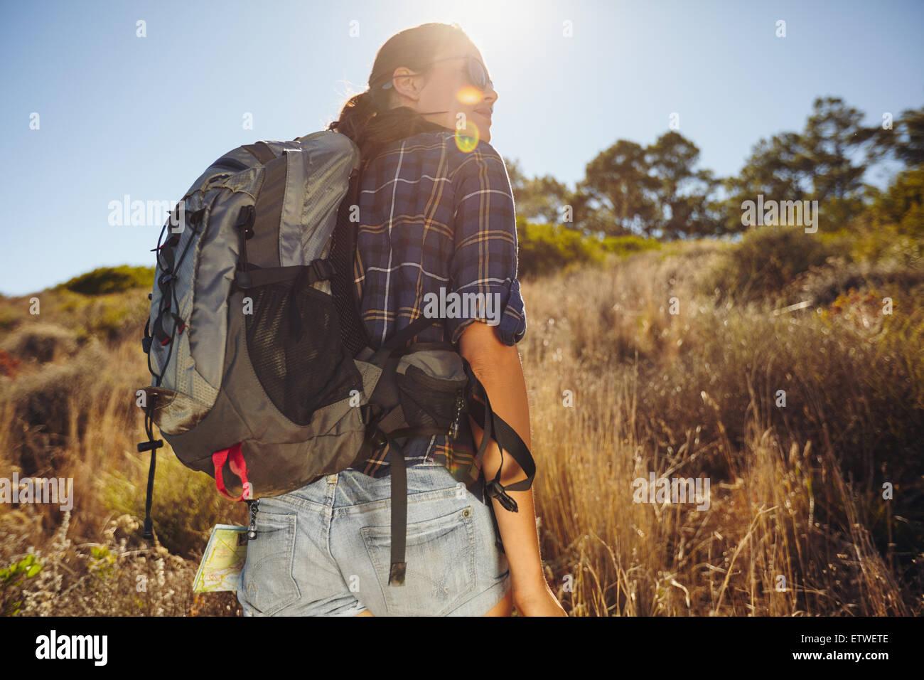 Vista posteriore del colpo di giovane donna escursionismo sul giorno di estate. Femmina caucasica escursionista Immagini Stock