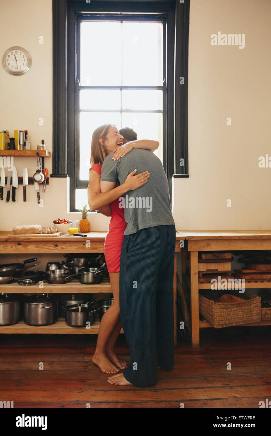 Felice giovane donna essendo abbracciato con il suo fidanzato in cucina. Allegro coppia giovane che abbraccia ogni Foto Stock