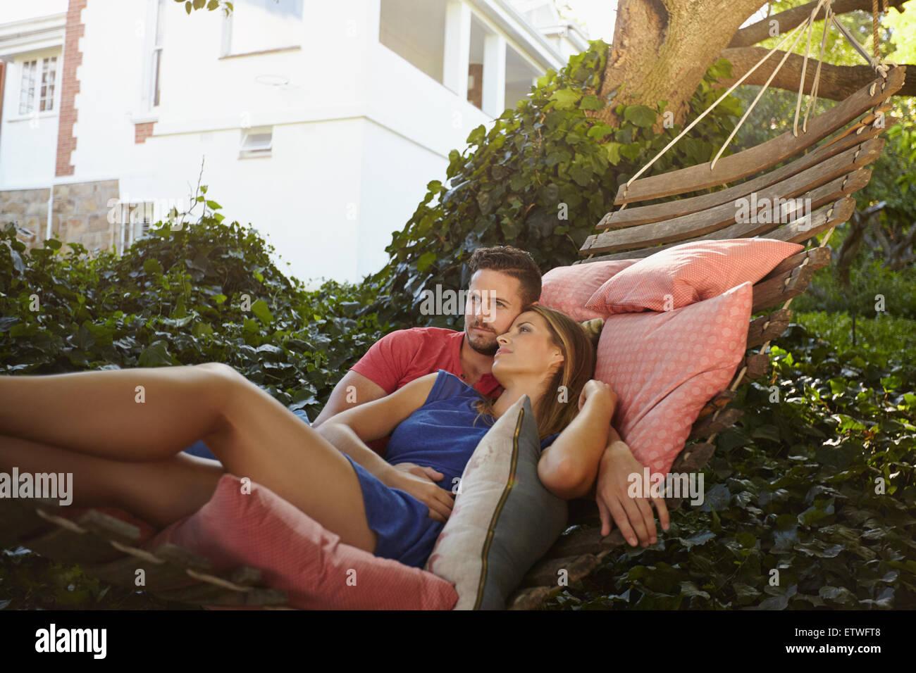 Coppia giovane rilassante su un giardino amaca. Essi sono alla ricerca di distanza nel pensiero. Rilassata l uomo Immagini Stock