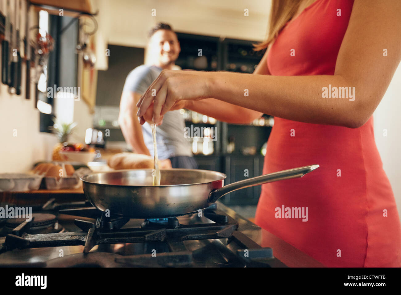 Ritagliato colpo di donna cracking mani un uovo su una padella sul fornello. Femmina di preparare la colazione con Immagini Stock