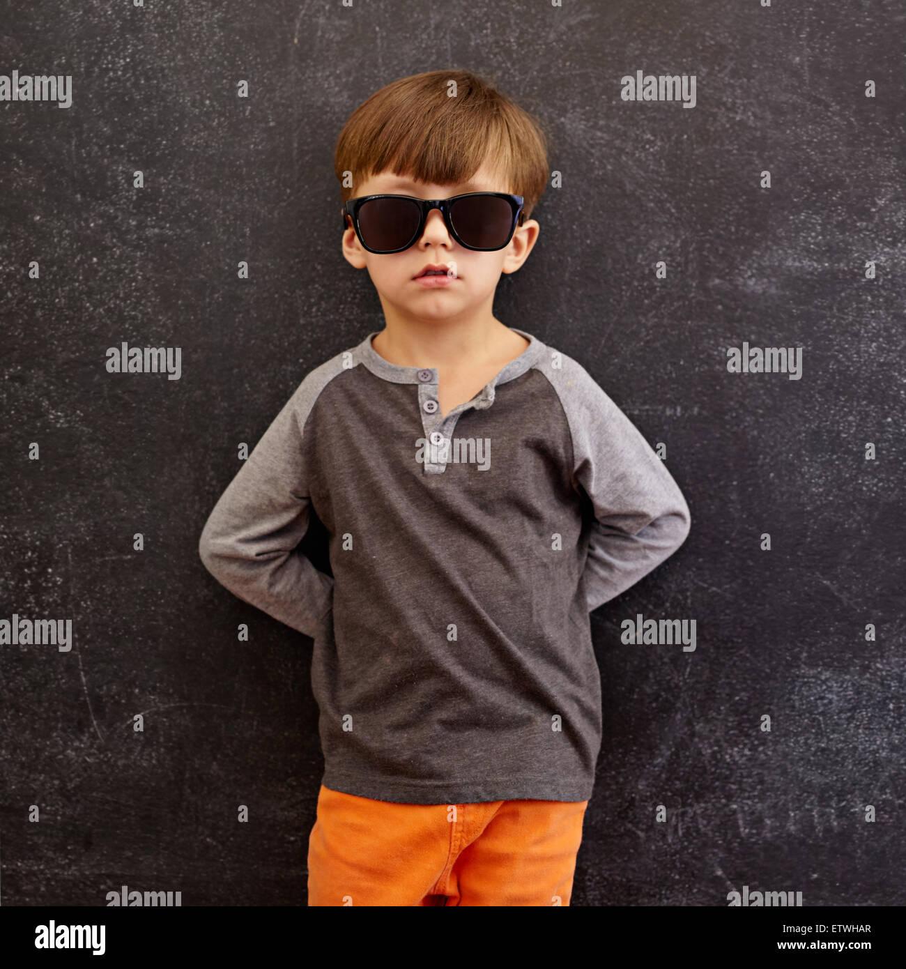 Ritratto di Innocenzo ragazzino indossando occhiali da sole. Little Boy appoggiata su una lavagna. Composizione Immagini Stock