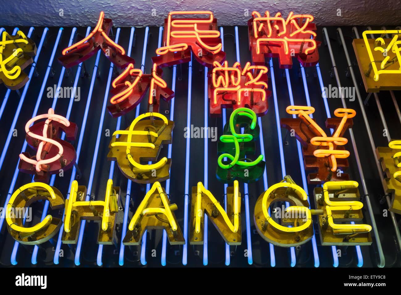 Luci al neon elencando varie monete al di sopra di cambio valuta Negozio di notte a Hong Kong Cina Immagini Stock