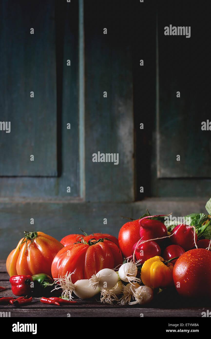 Cumulo di fresche e mature verdure colorate i pomodori, i peperoncini, il cipollotto e il mazzetto di ravanello Foto Stock