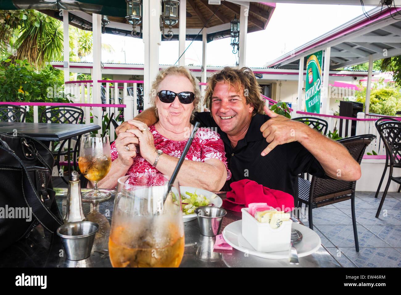 A 78 anni donna caucasica è imbarazzato da un estraneo abbraccio sulla terrazza di un caffè sulla spiaggia. Immagini Stock