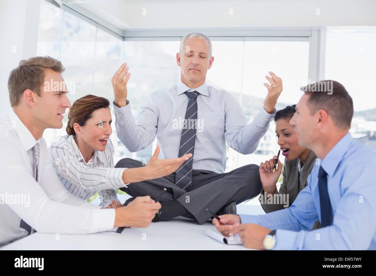 Imprenditore rilassante sulla scrivania con sconvolto i colleghi circa Immagini Stock