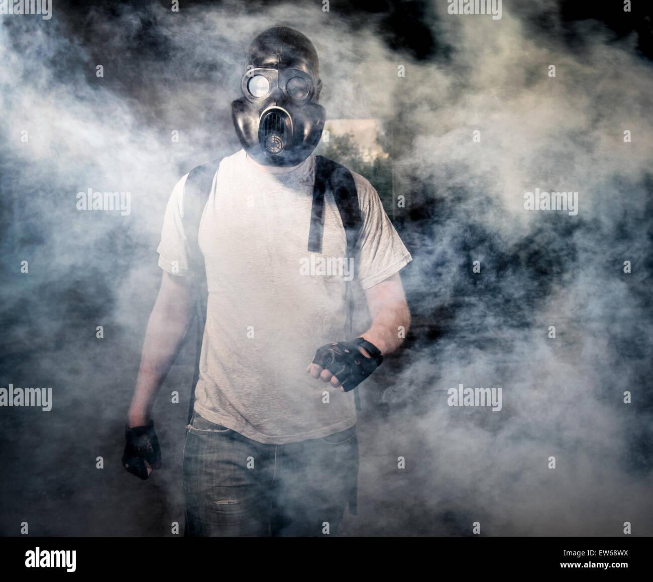 Uomo in una maschera a gas a piedi attraverso il fumo Immagini Stock