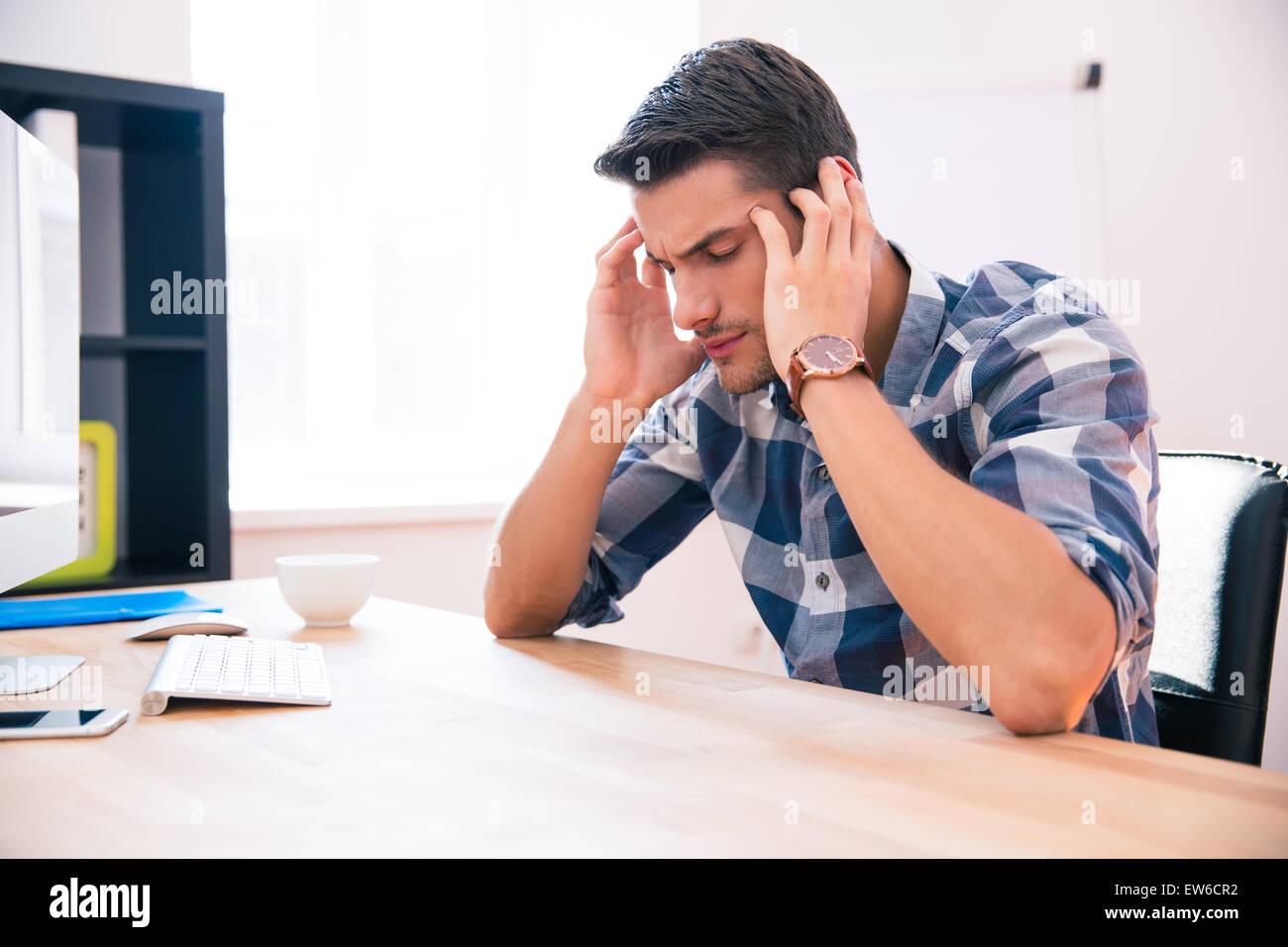 Malinconici imprenditore seduti a tavola in office Immagini Stock