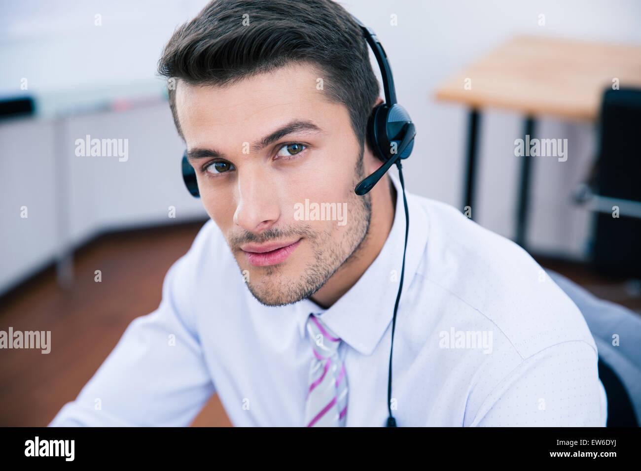 Ritratto di un bel operatore maschio con cuffia guardando la fotocamera in ufficio Immagini Stock