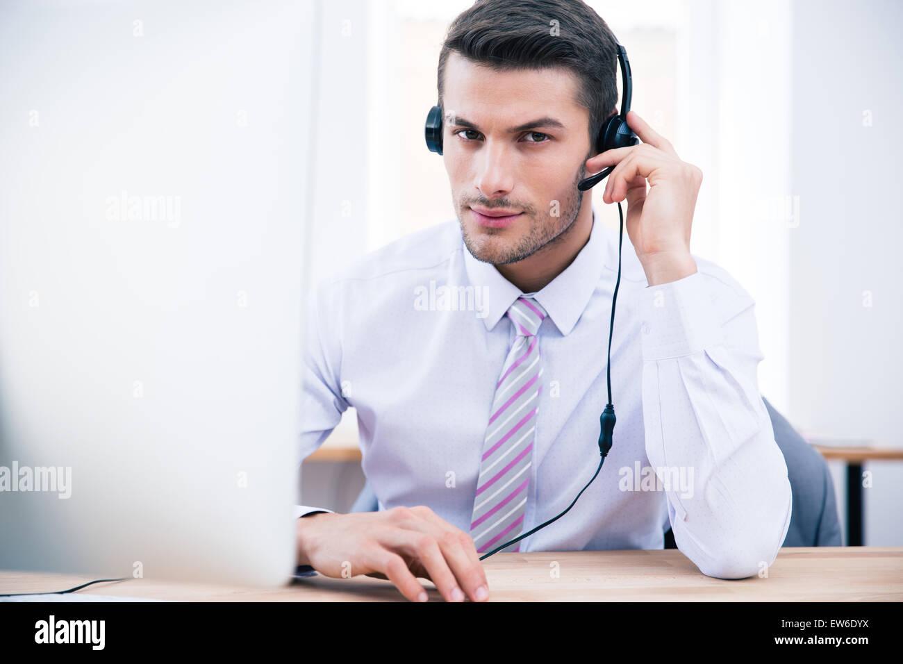 Fiducioso maschio operatore seduto al suo posto di lavoro in ufficio e guardando la fotocamera Immagini Stock