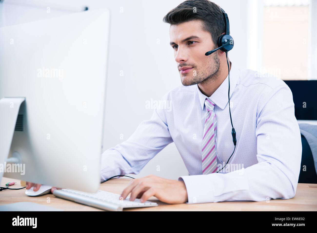 Bel maschio operatore che lavora sul PC in ufficio Immagini Stock