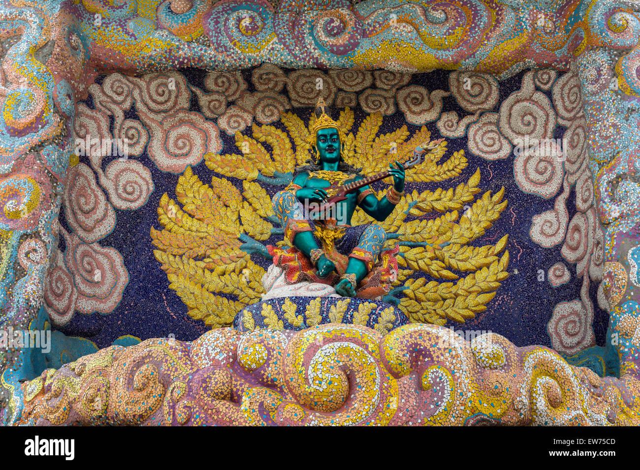 Dettaglio, musicista con i tradizionali strumenti a corda Phin sopra l'entrata del tempio di elefante Thep Vihara Immagini Stock