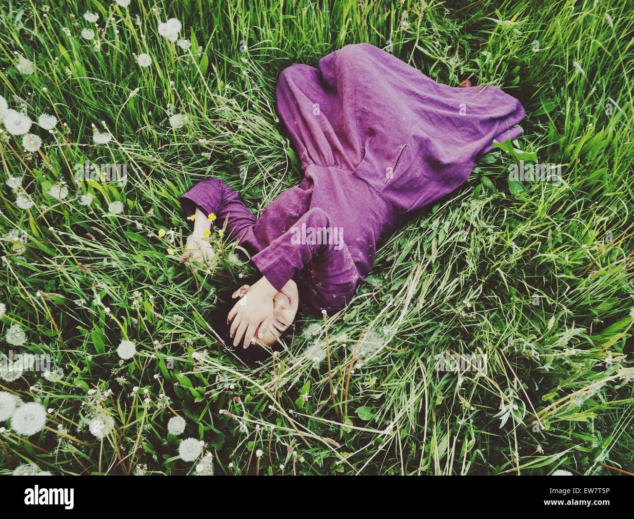 Vista in elevazione di una donna sdraiata in erba con la mano che copre il volto Foto Stock