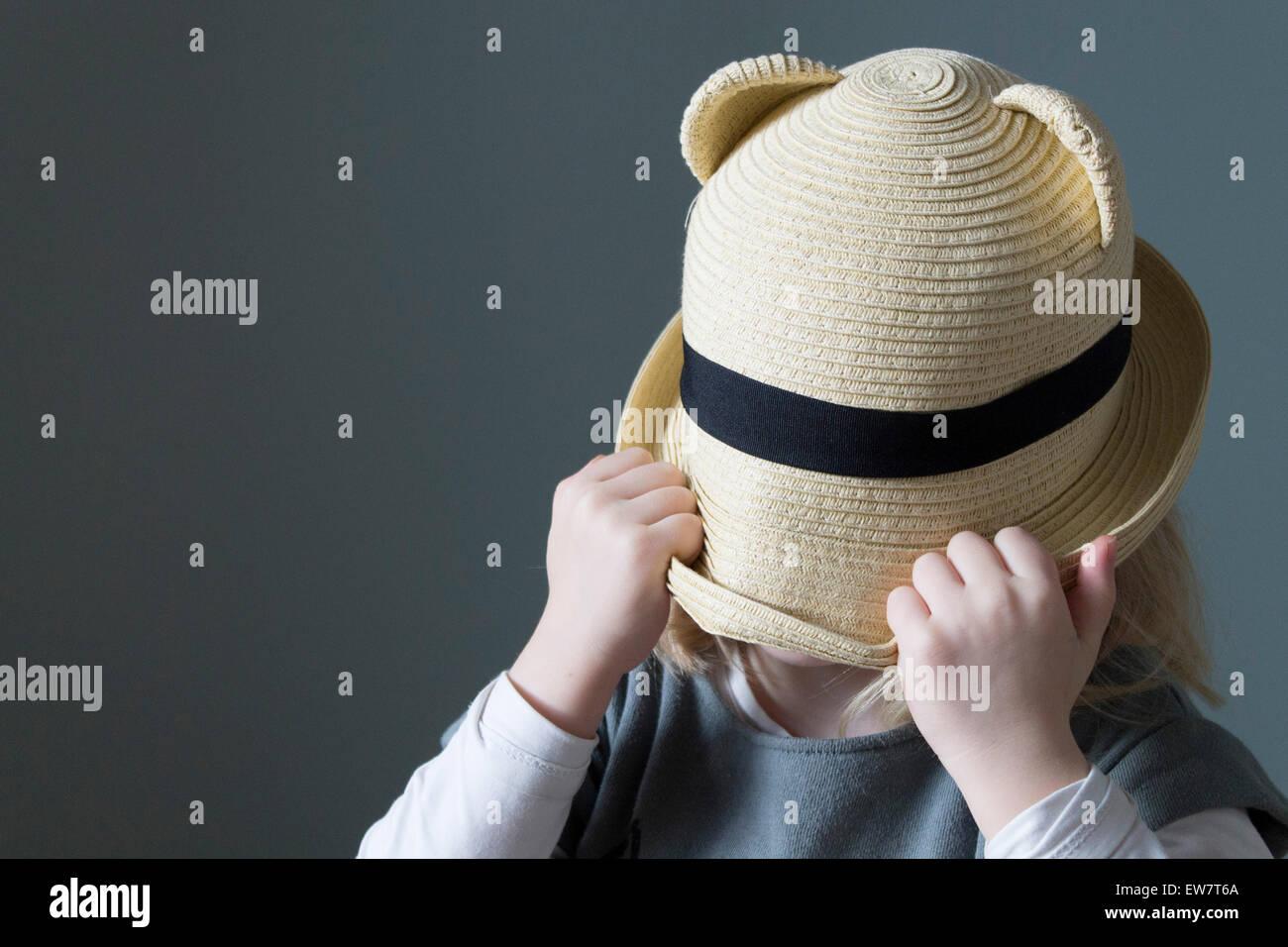Ragazza tirando il suo cappello verso il basso sopra il suo volto Immagini Stock