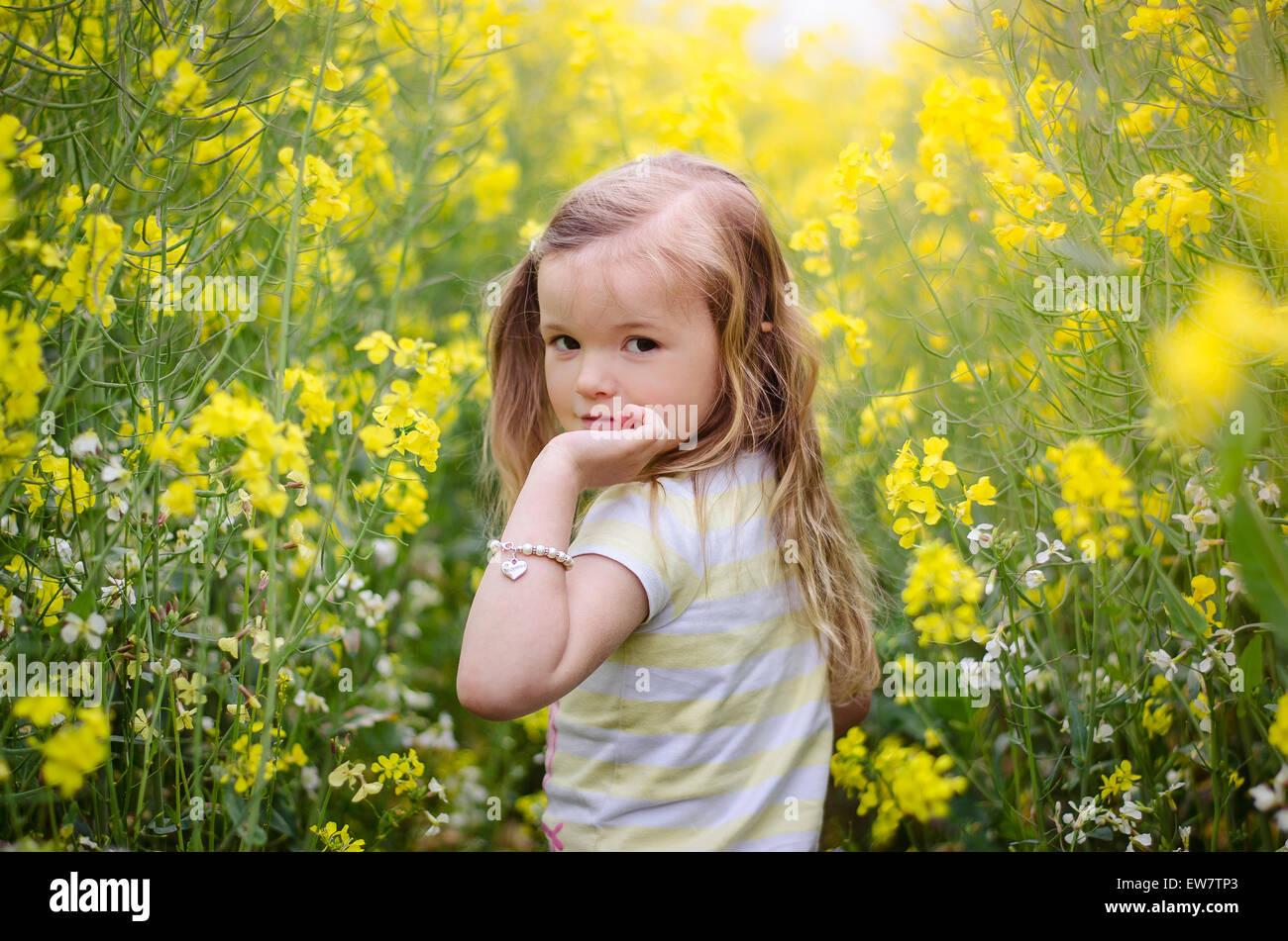 Ragazza guardando sopra la sua spalla in un prato di fiori gialli Immagini Stock