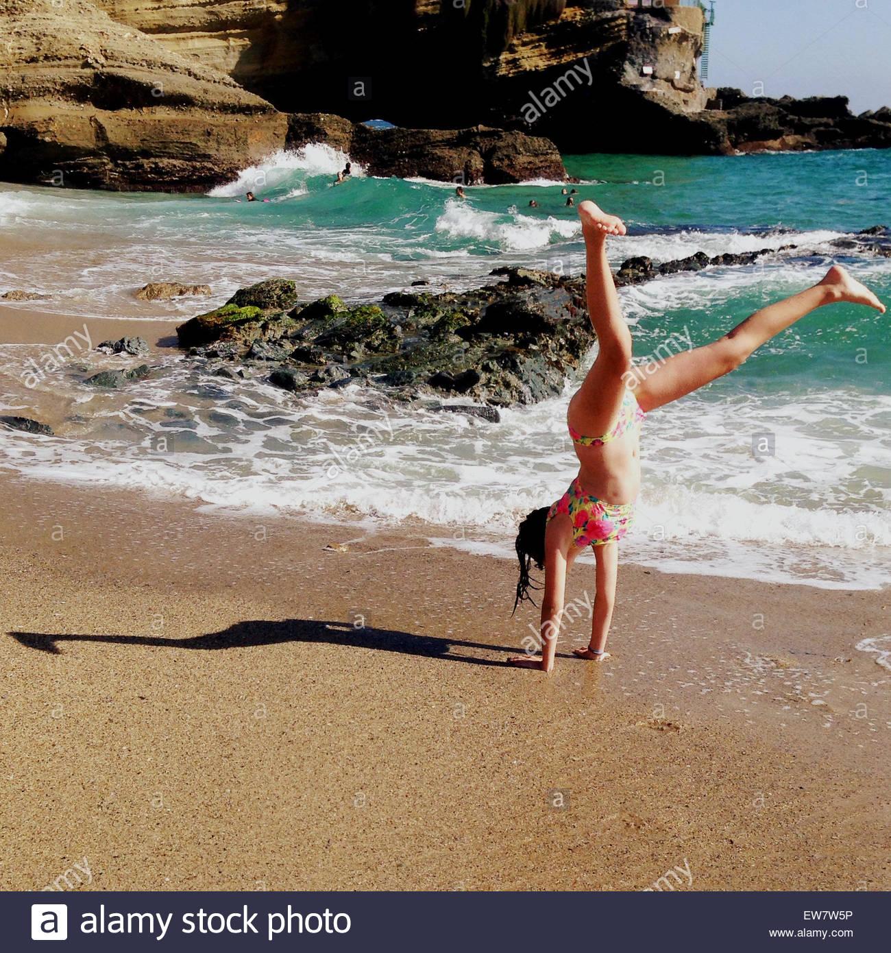Ragazza facendo un appoggiate sulla spiaggia facendo un'ombra che assomiglia a una giraffa Immagini Stock