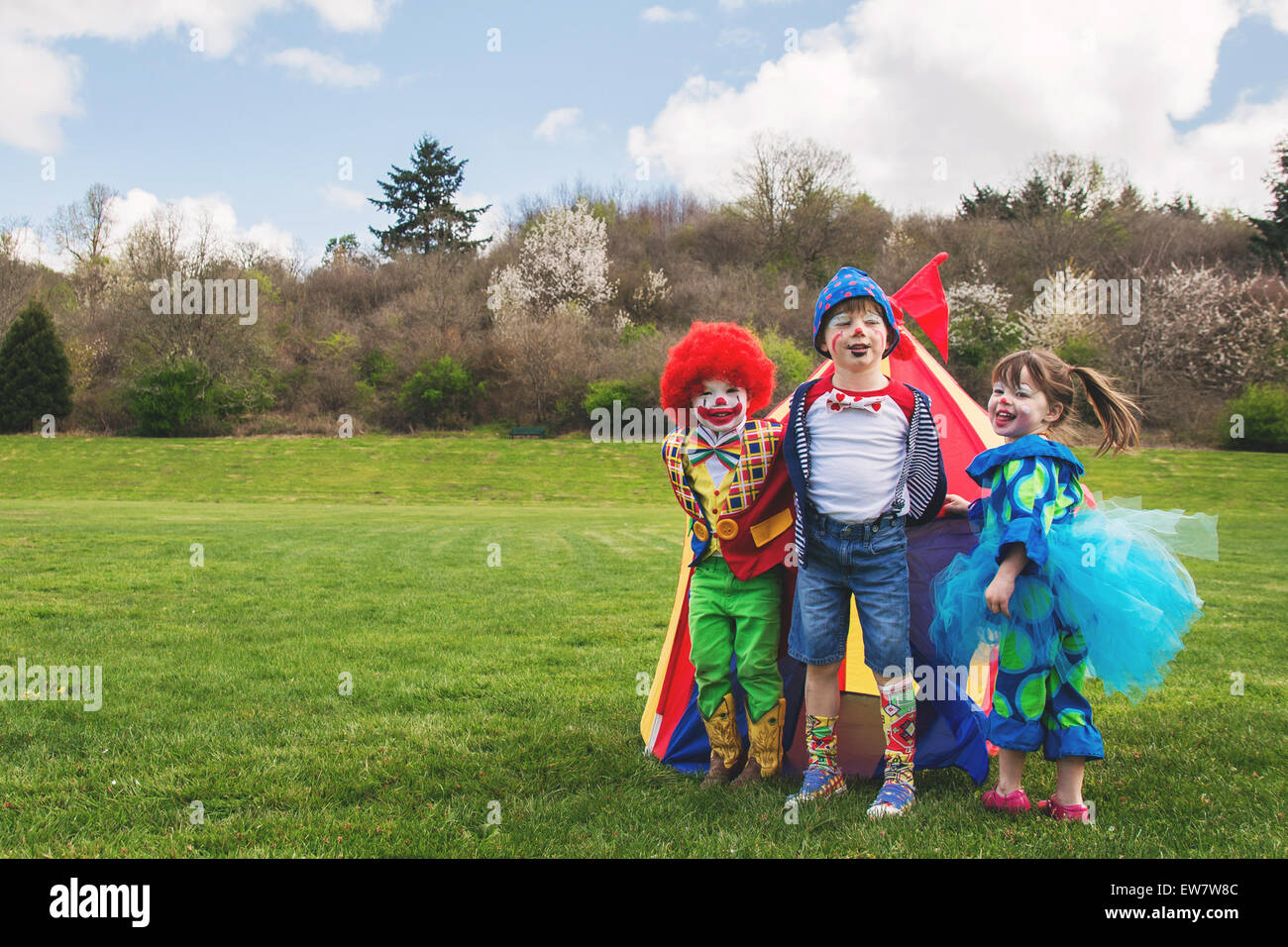 Tre bambini sorridenti vestiti come pagliacci Immagini Stock