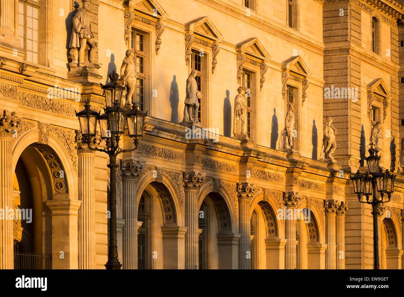Tramonto su statue lungo la parete esterna del Musee du Louvre, Parigi, Francia Immagini Stock