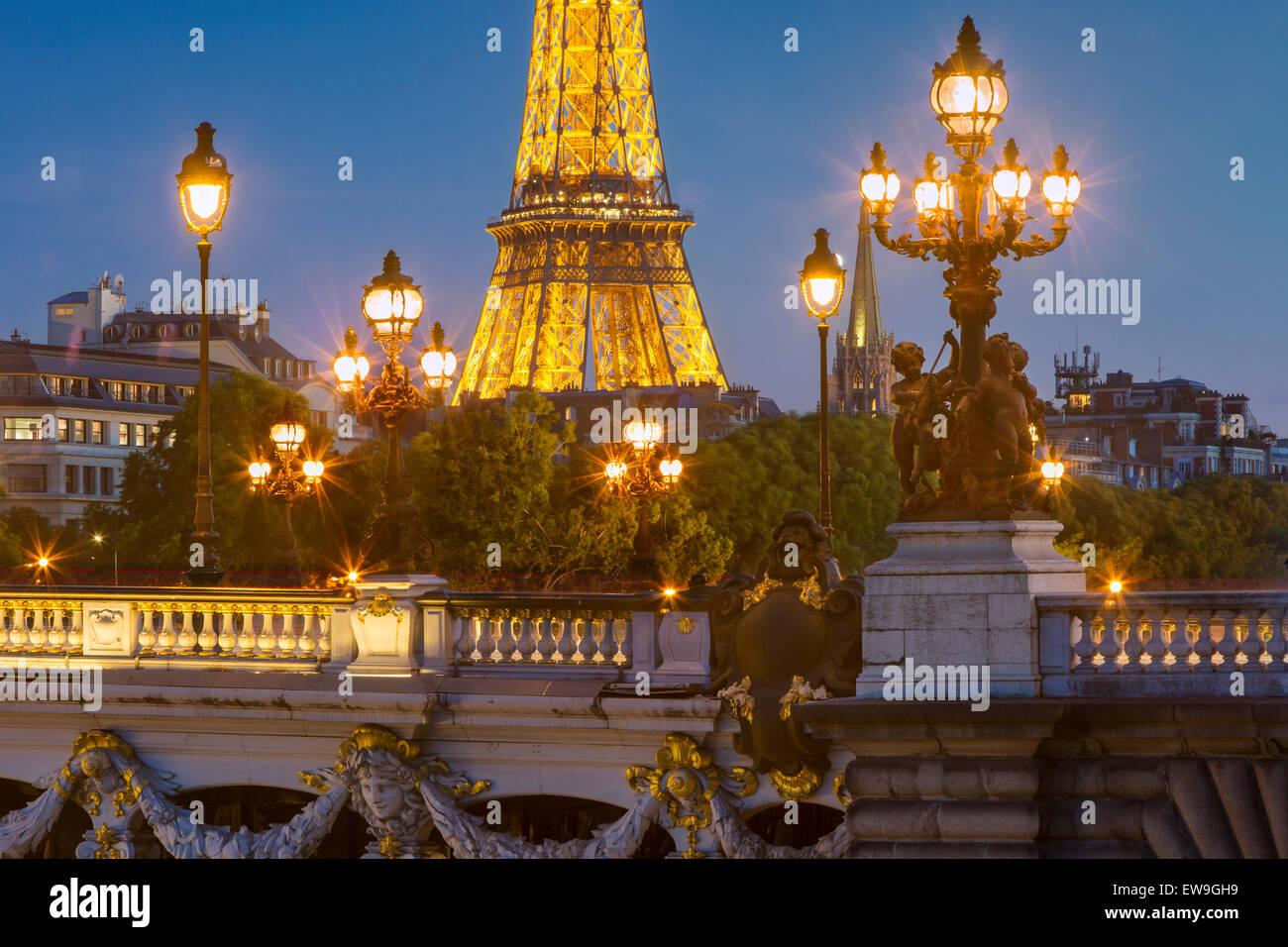 Twilight su luci di Pont Alexandre III con la Torre Eiffel al di là, Parigi, Ile-de-France, Francia Immagini Stock