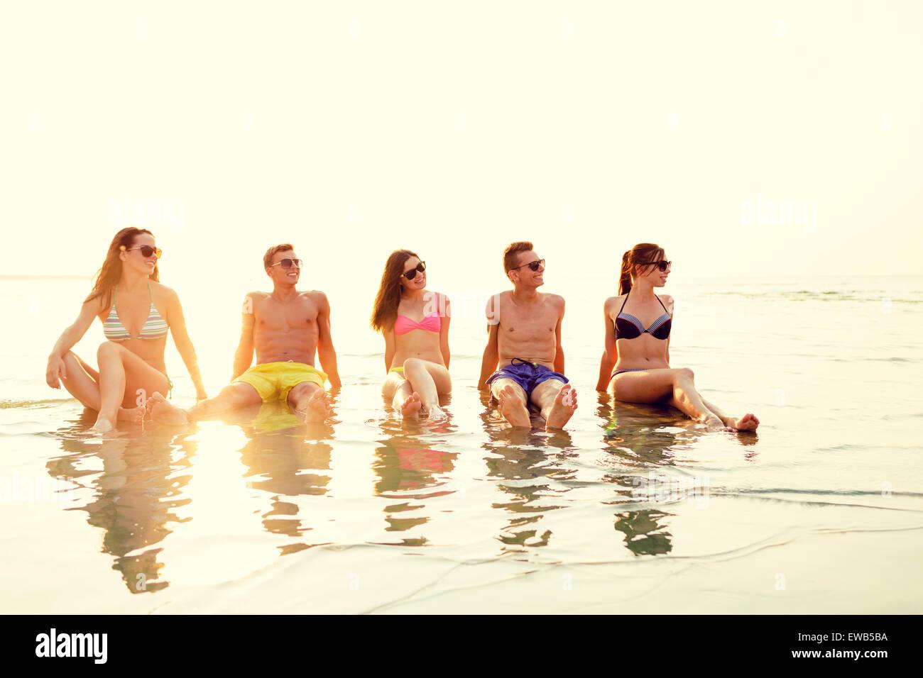 Sorridente amici in occhiali da sole sulla spiaggia di estate Immagini Stock