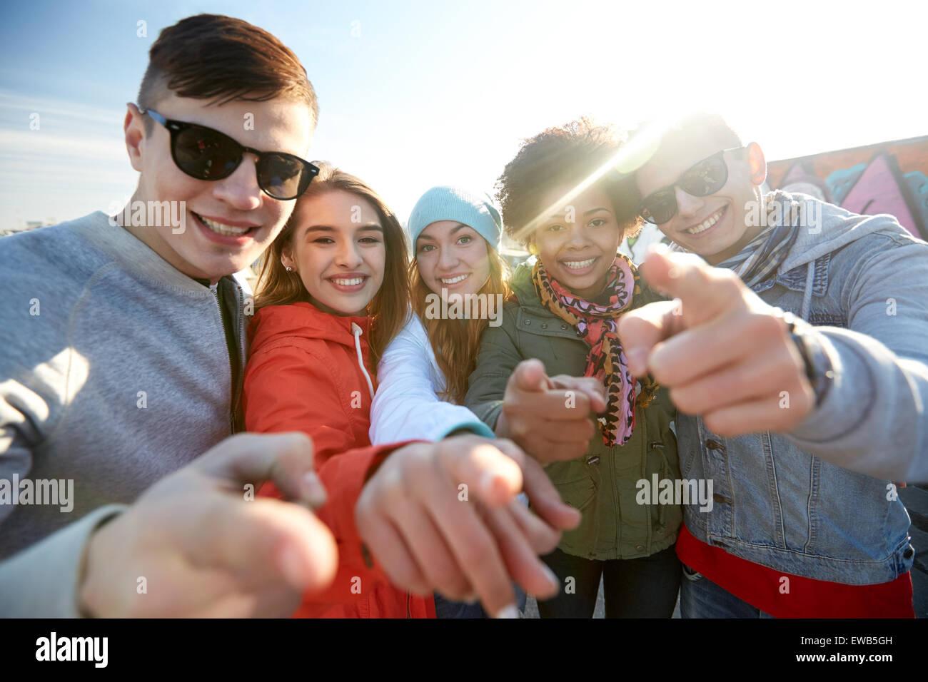 Happy amici adolescenti dita di puntamento su strada Immagini Stock