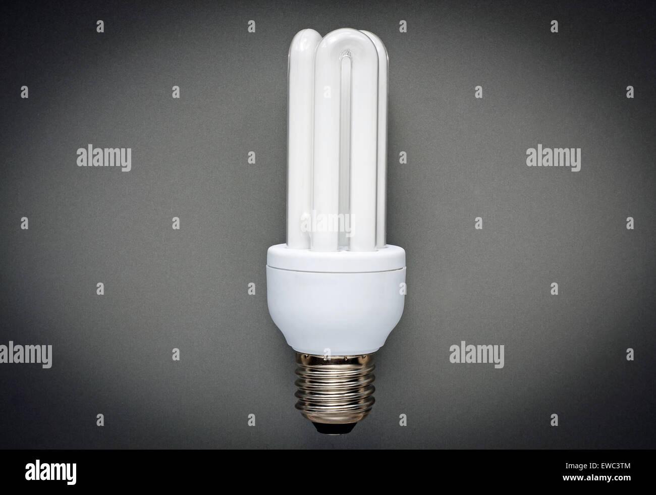 Risparmio energetico lampada su sfondo grigio Immagini Stock