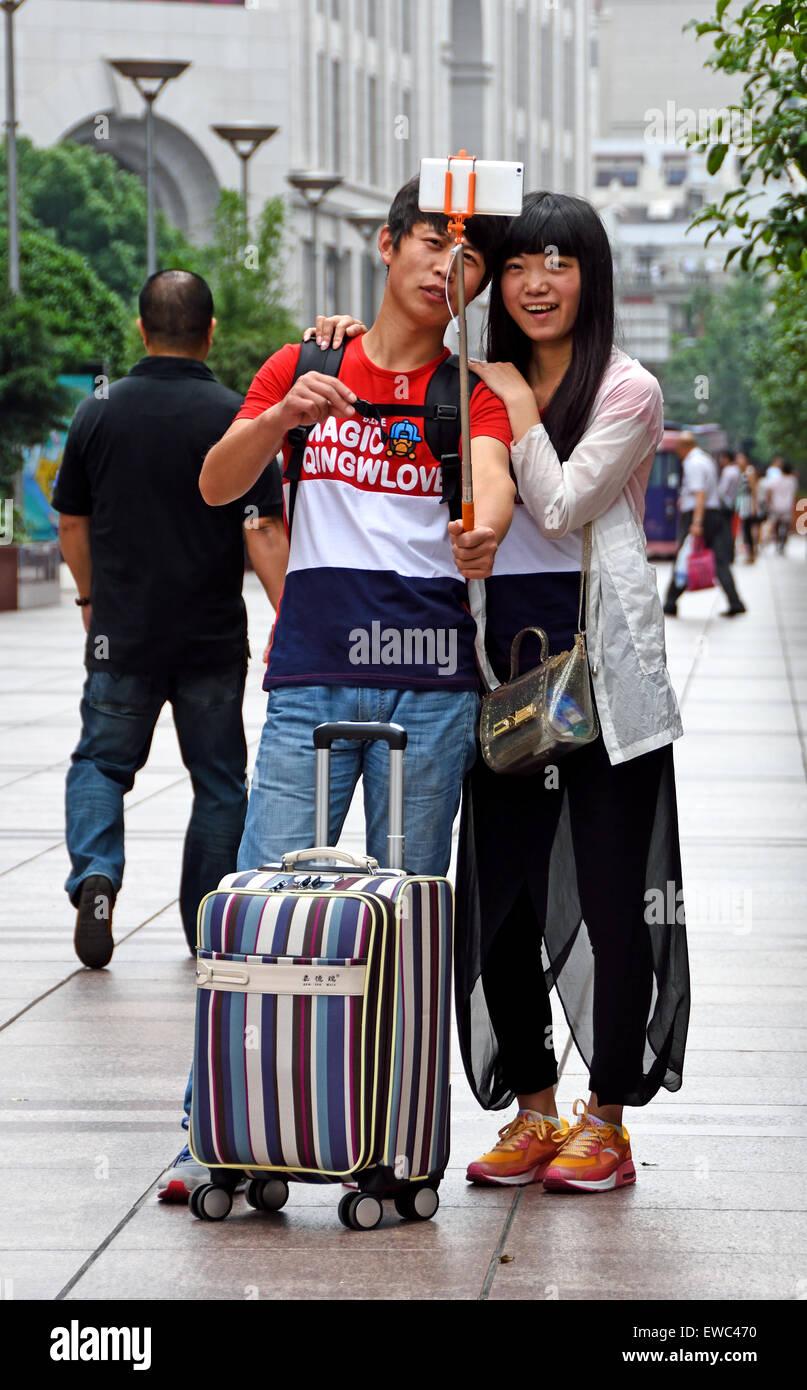 Stick selfie foto attraente bella giovani visitatori a Nanjing Road. Strada principale per lo shopping di Shanghai. Immagini Stock