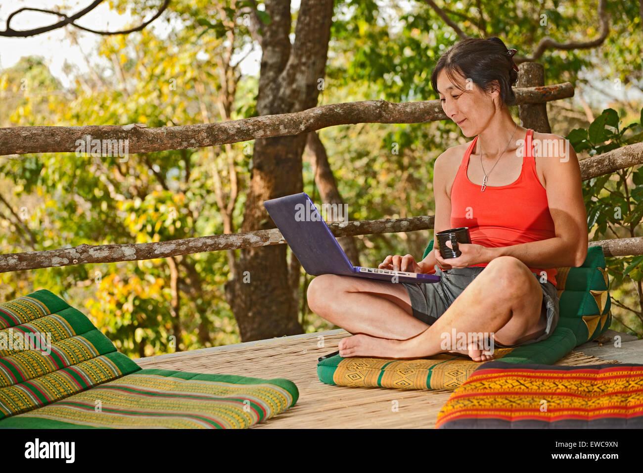 Donna seduta con il suo computer portatile su una terrazza all'aperto in corrispondenza di una street cafe nel Immagini Stock