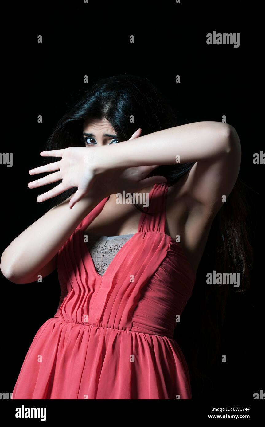 Spaventata donna in pericolo nasconde il viso con le mani Immagini Stock