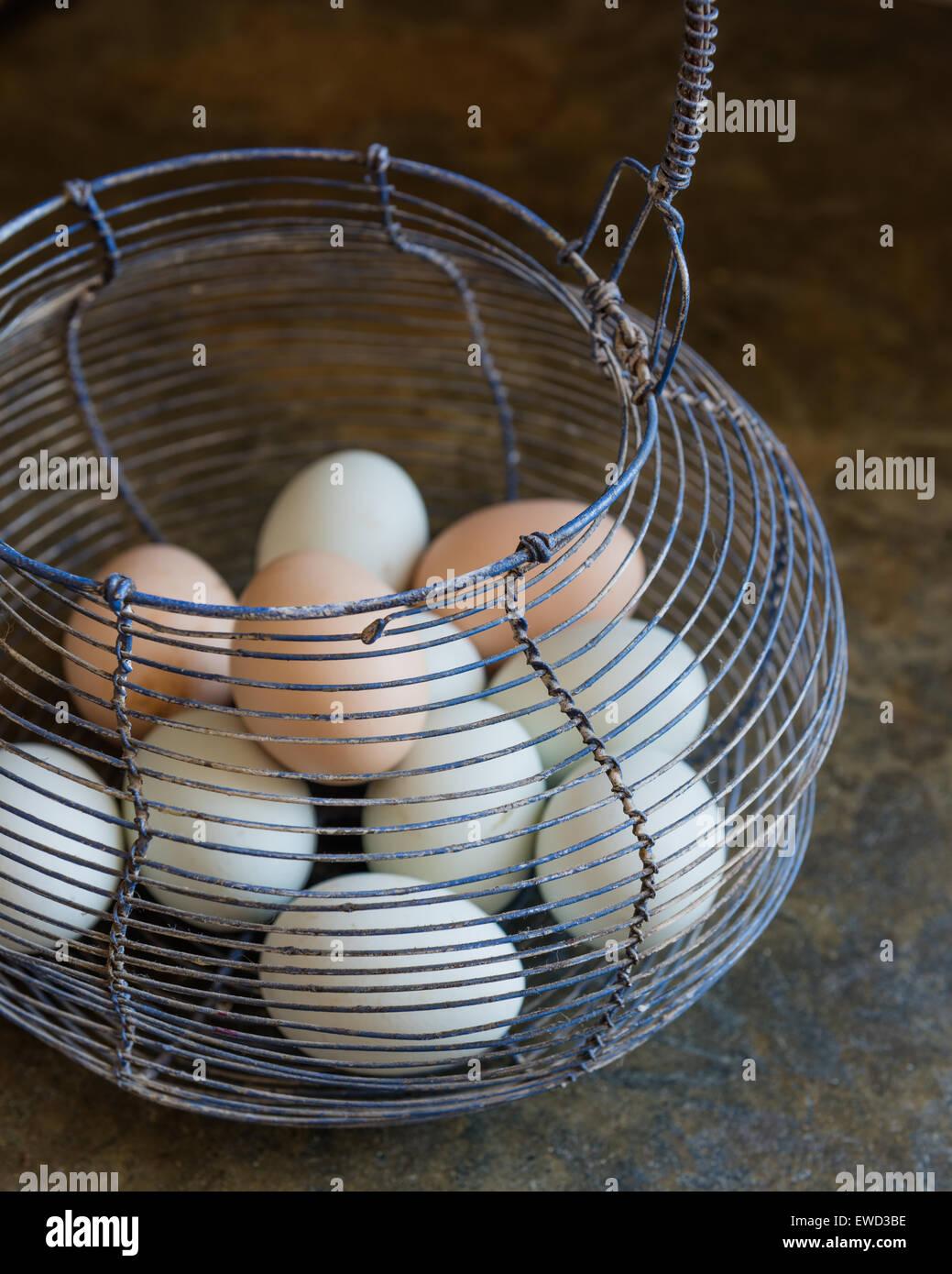 Le uova in un vintage Cestello in filo metallico Immagini Stock
