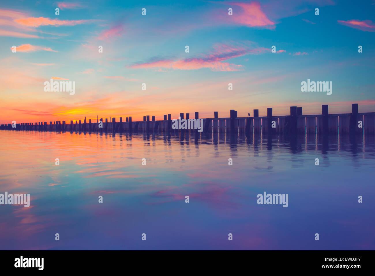 Splendido oceano scena con molo in legno al tramonto Immagini Stock