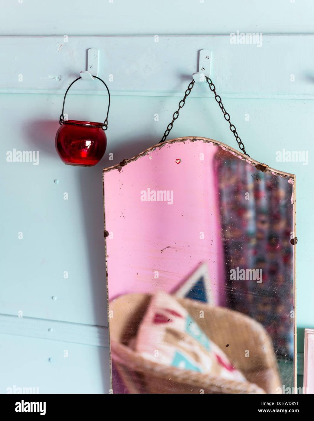 Specchio vintage e portacandele appeso dal gancio appendiabiti cremagliera sul cielo blu parete colorata Immagini Stock