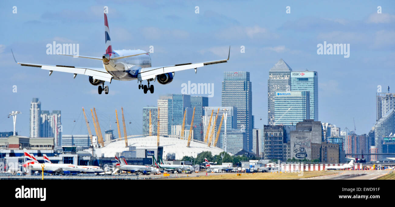 Volo British Airways in atterraggio a London City Airport (Newham) con l'O2 Arena e Canary Wharf (Tower Hamlets) Immagini Stock
