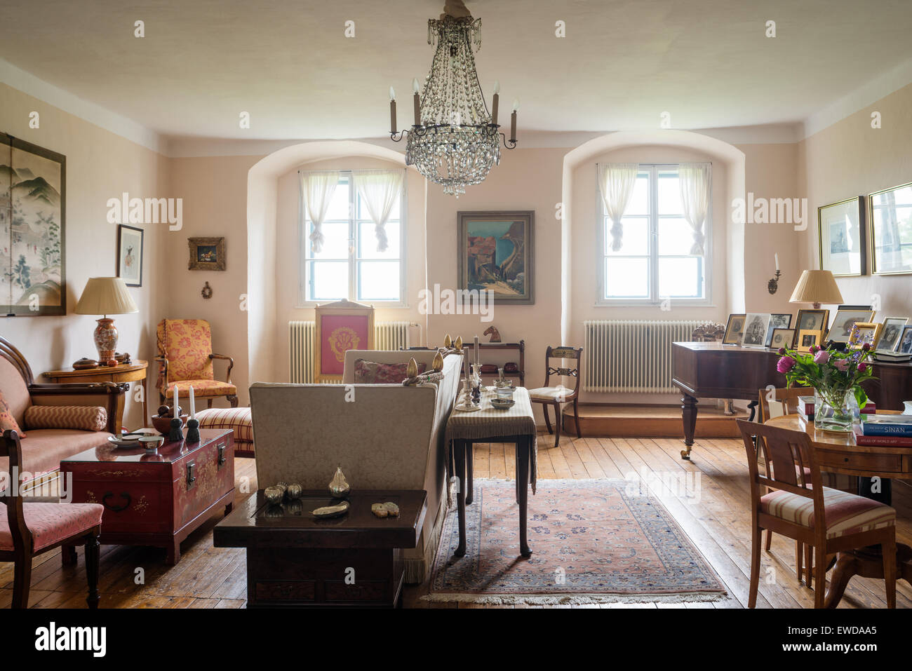 Knole divano e tappeto pakistano in soggiorno con rosso cinese torace laccato e pianoforte Immagini Stock