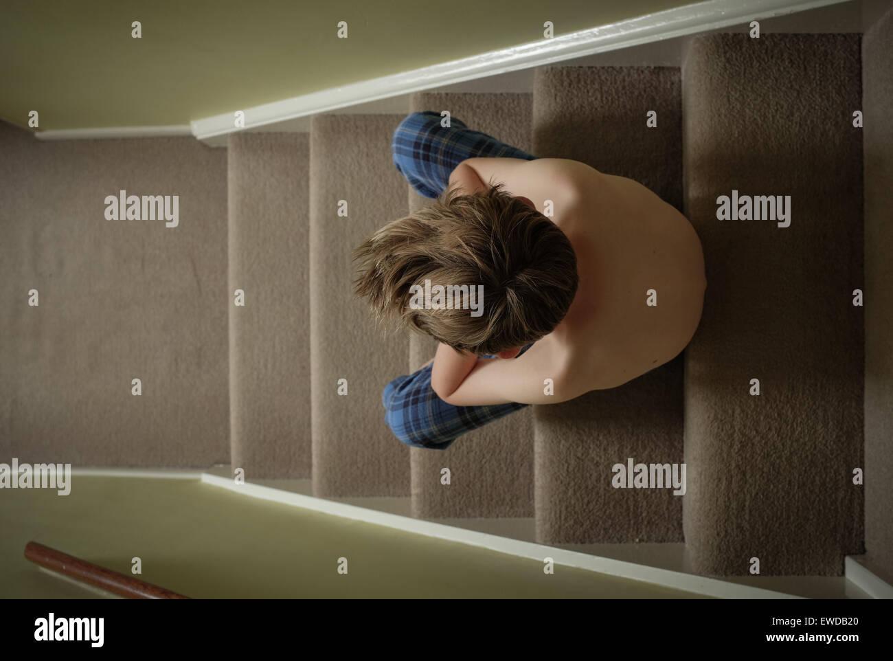 Un bambino seduto sulle scale con la testa tra le mani cercando sconvolto Immagini Stock
