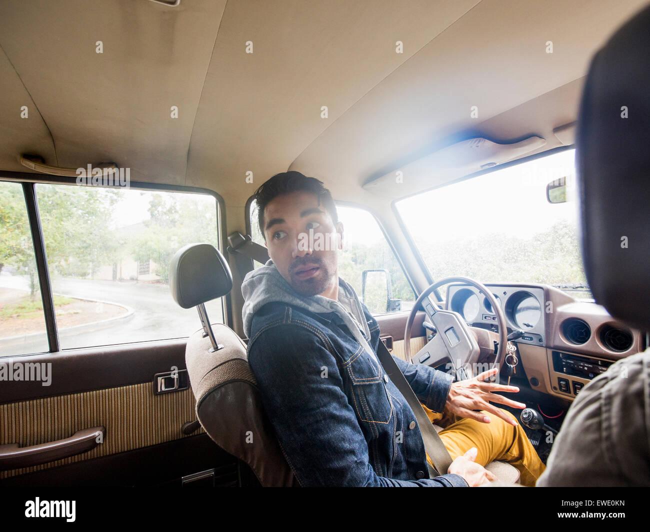 Giovane uomo in auto nel sedile del guidatore, guardando sopra la sua spalla Immagini Stock