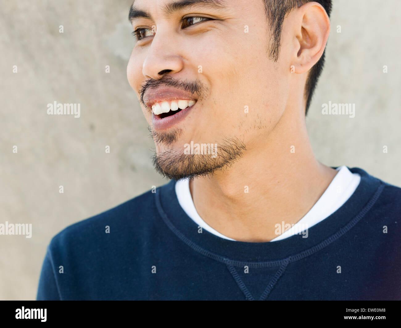 Ritratto di un sorridente giovane asiatica di razza mista barba stoppie guardando lateralmente Immagini Stock