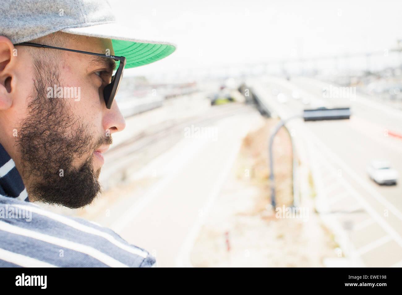 Close up di un barbuto giovane uomo che indossa gli occhiali da sole e un  cappello 453e1dee84e4