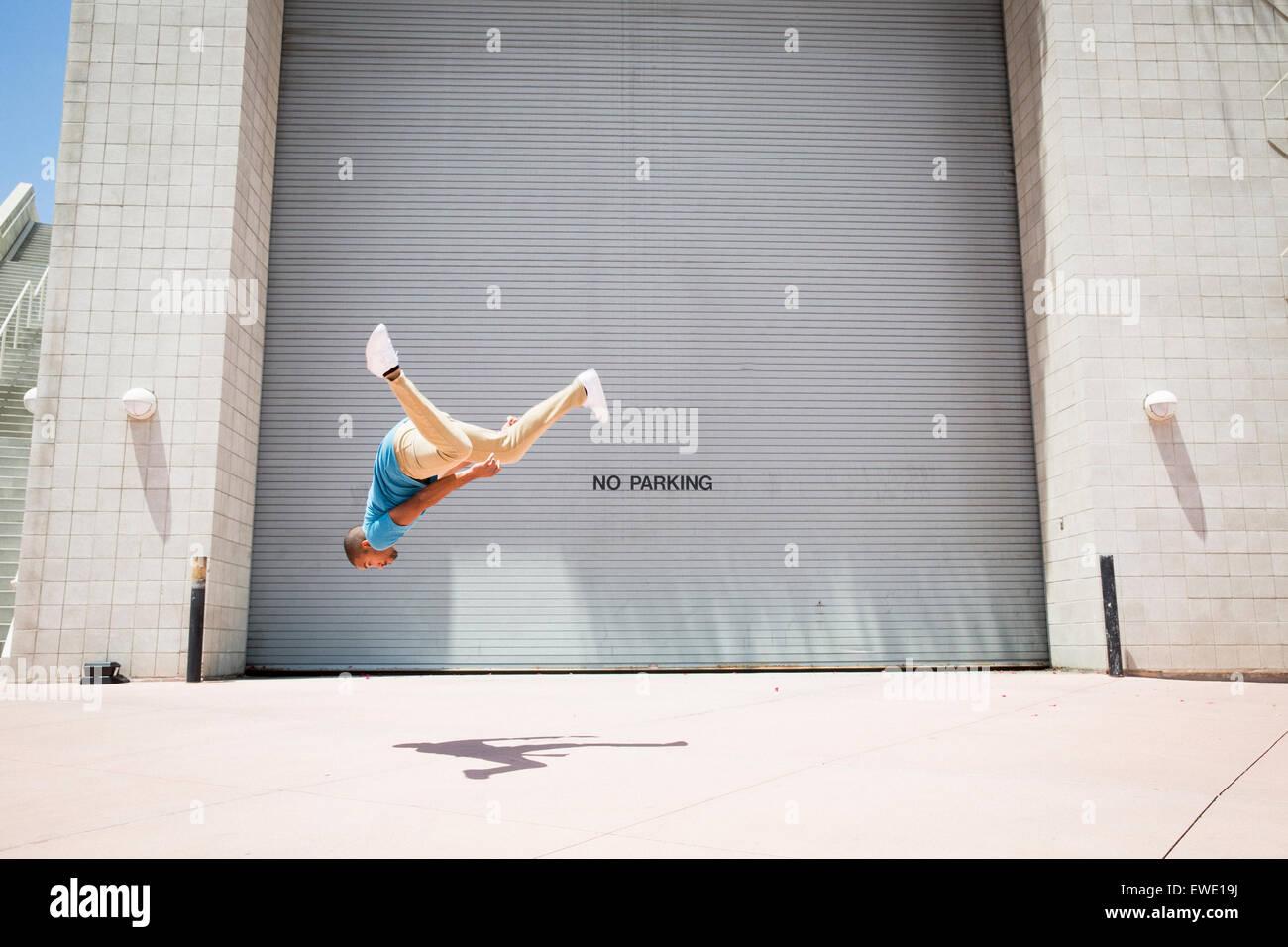 Giovane uomo somersaulting sulla strada ostacolo corso parkour free running Immagini Stock