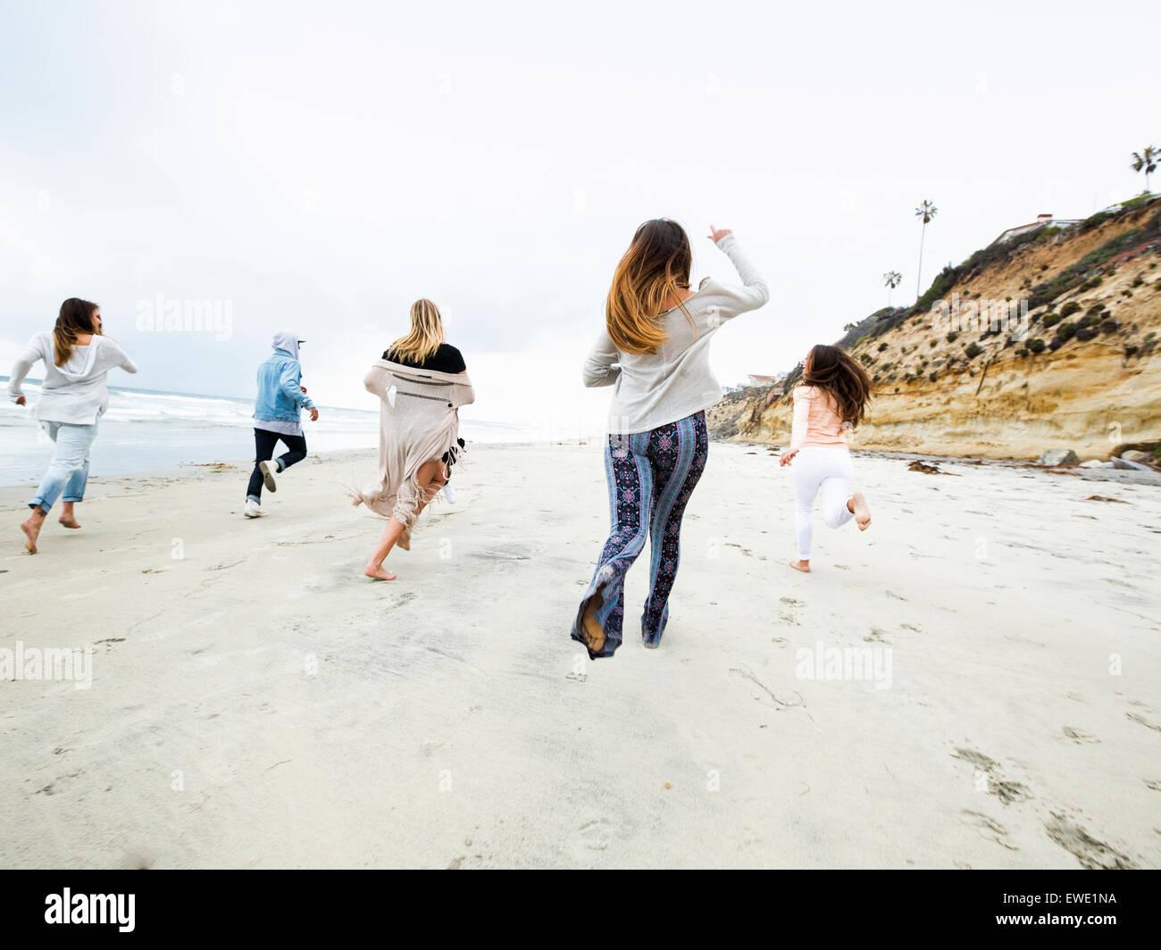 Un gruppo di giovani uomini e donne in esecuzione su una spiaggia, divertimento Immagini Stock