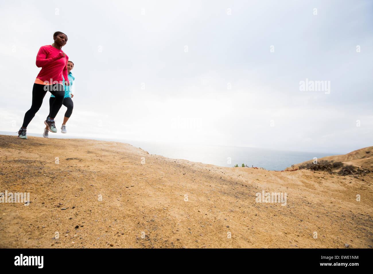 Due donne a fare jogging lungo la costa di idoneità Immagini Stock