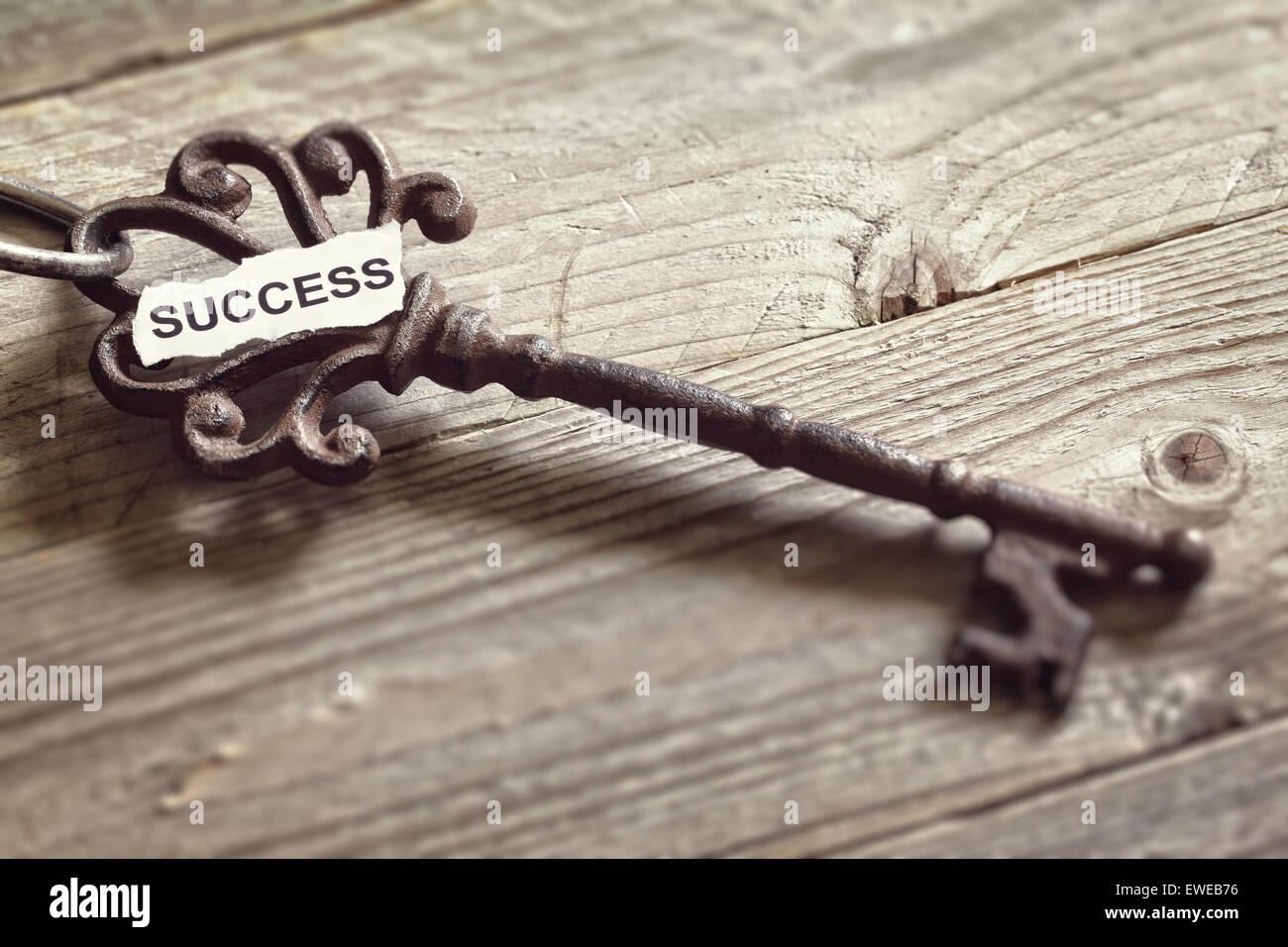 Chiave di antiquariato con successo la parola scritta su carta in appoggio sulla superficie di legno del concetto Immagini Stock