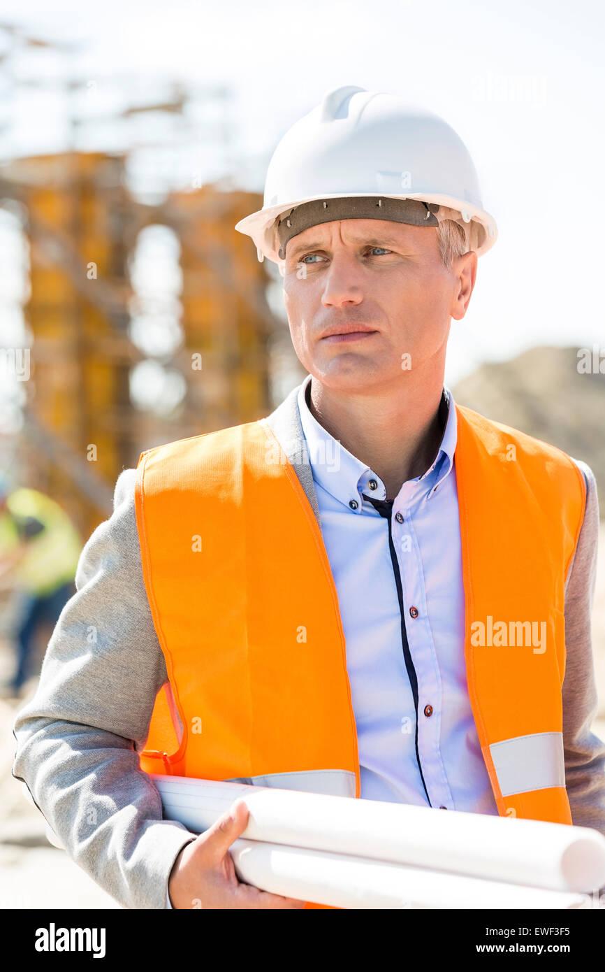 Architetto pensieroso guardando lontano tenendo blueprint al sito in costruzione Immagini Stock