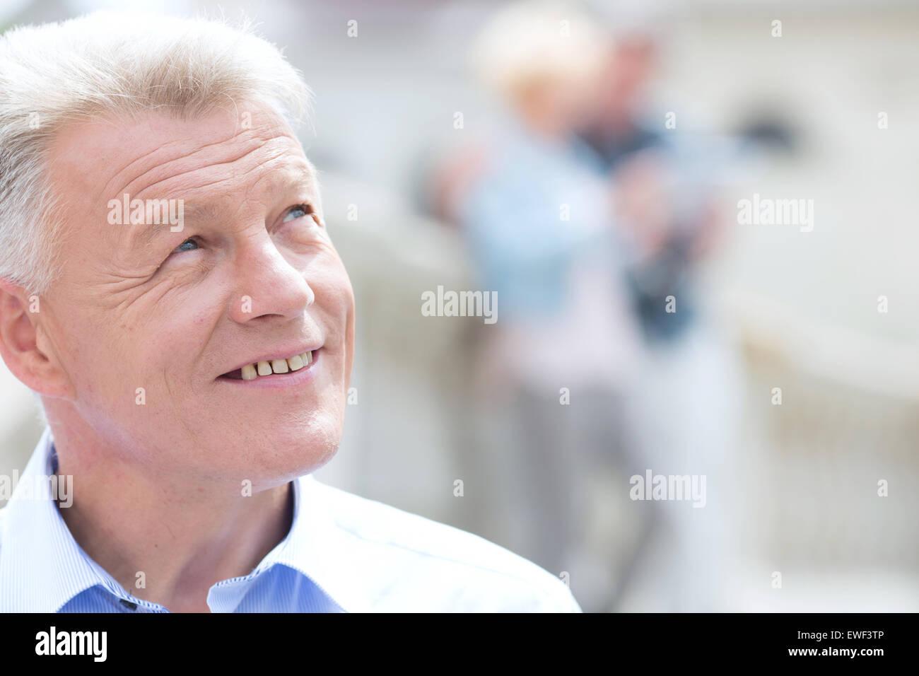 Close-up di uomo sorridente che guarda lontano all'aperto Immagini Stock