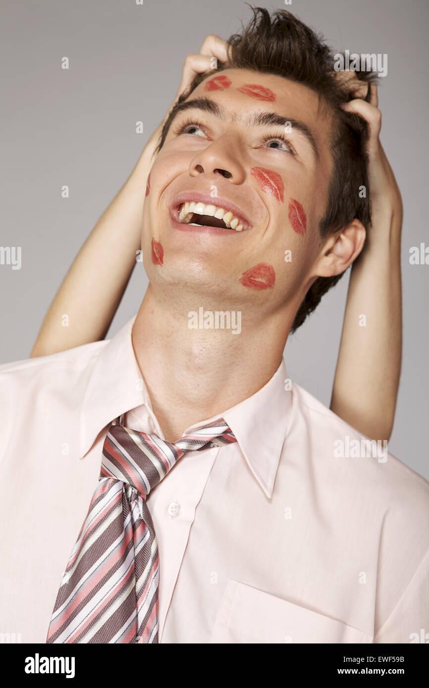 Giovane imprenditore caucasico con il rossetto kiss mark sulla sua guancia Immagini Stock