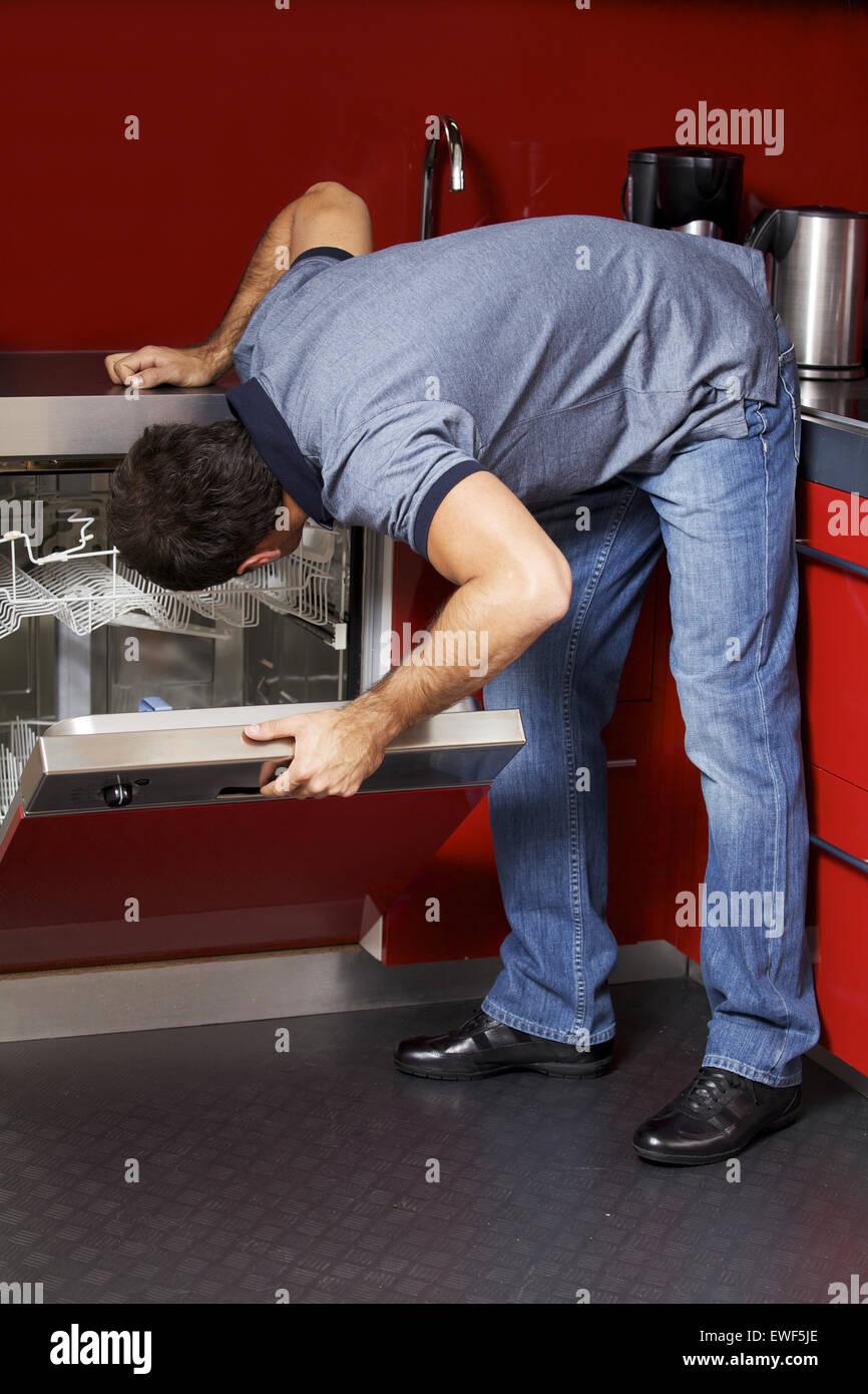 Giovane uomo cercando in lavastoviglie Immagini Stock