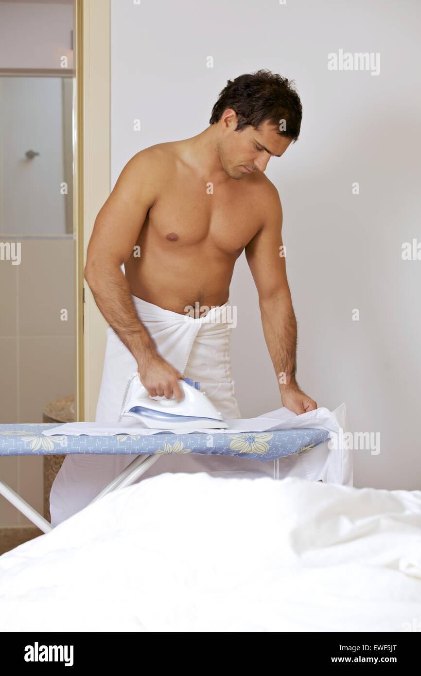 Uomo in asciugamano abiti da stiro su un supporto Immagini Stock