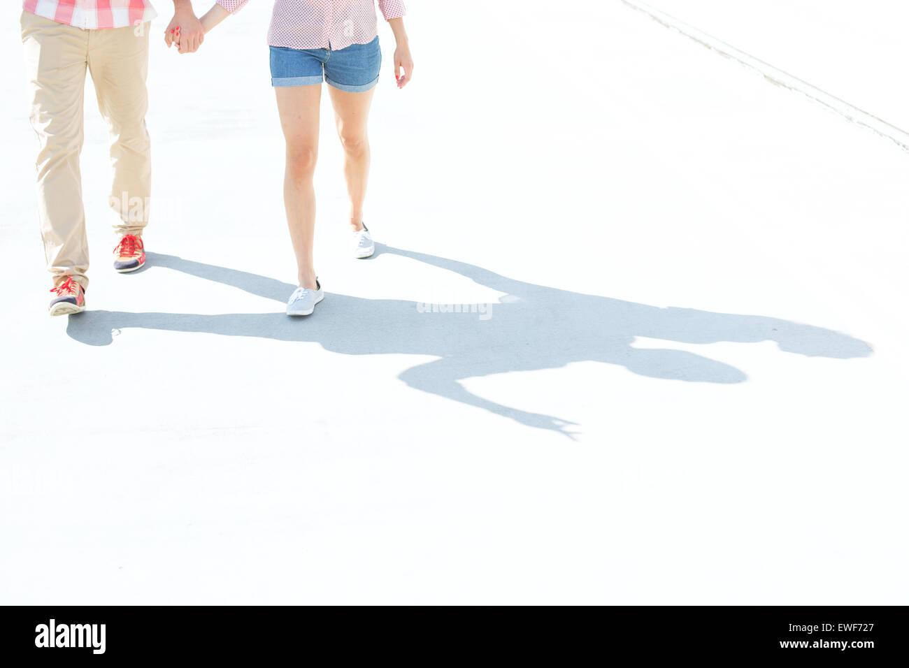 Sezione bassa del giovane camminando sulla strada Immagini Stock