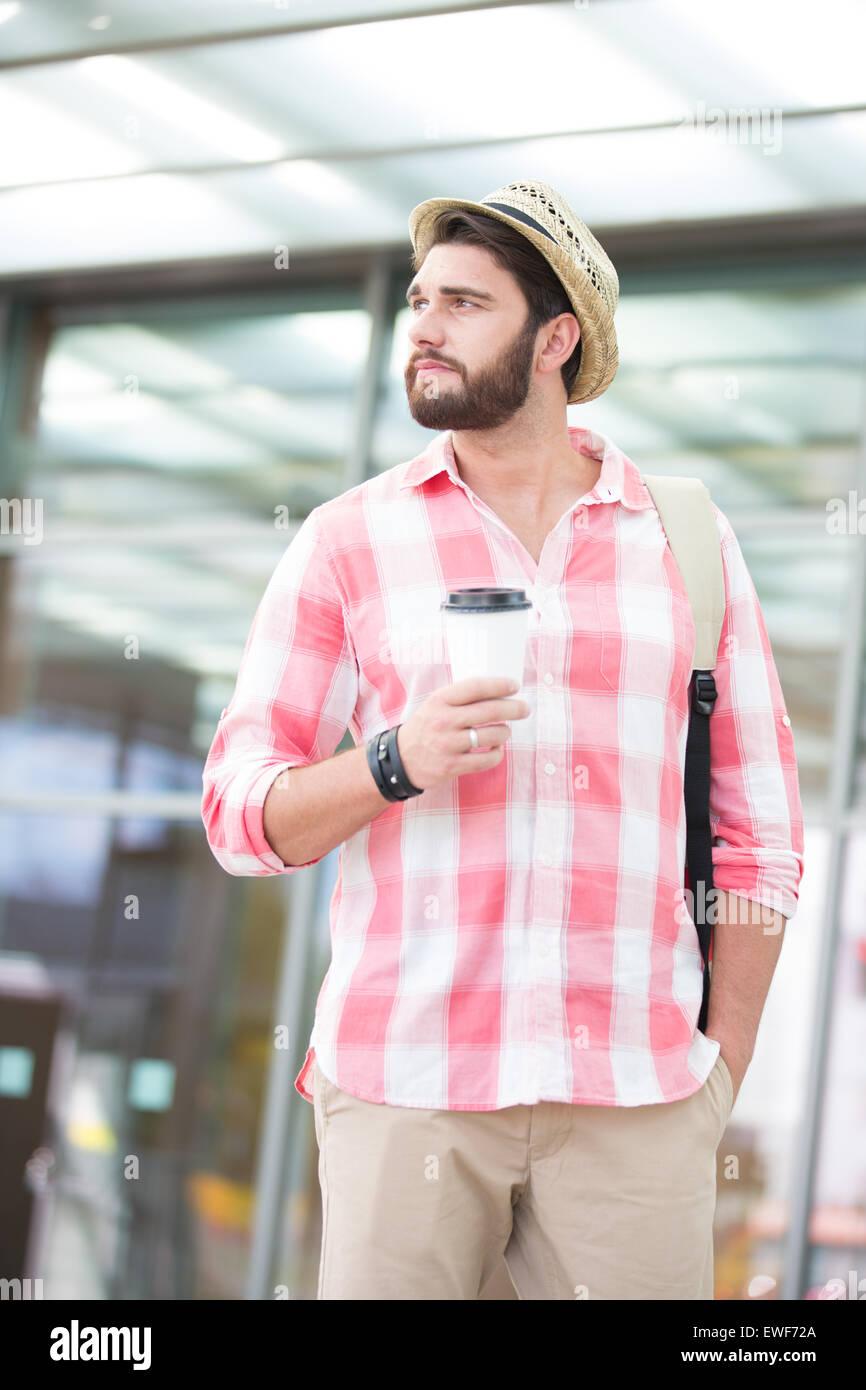 Considerato l uomo che guarda lontano tenendo tazza monouso in città Immagini Stock